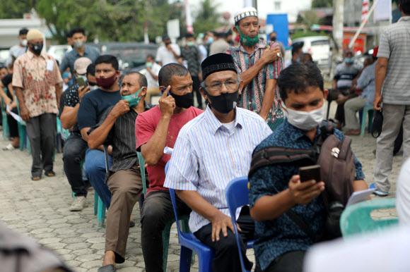 백신 접종 대기 중인 인니인들 - 7월 15일 인도네시아 반다아체에서 현지인을 대상으로 한 대량 백신 접종 중에 사람들이 시노백 백신을 받기 위해 대기하고 있다. 인도네시아는 대유행 초기부터 코로나19 환자 수가 26만명에 이르면서 백신 접종 프로그램에 속도를 내고 있다. EPA 연합뉴스 2021-07-15