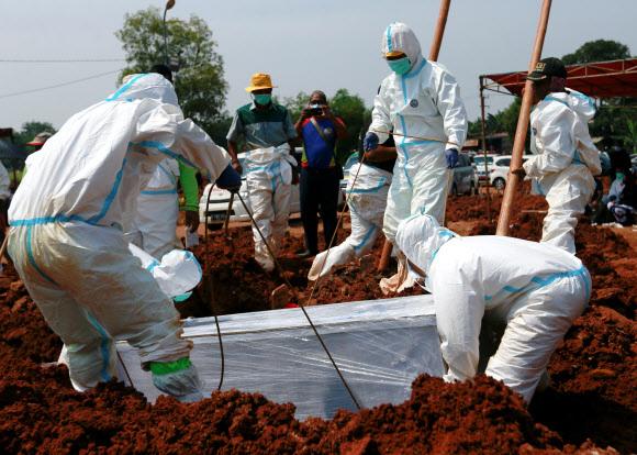 - 인도네시아 자카르타 외곽의 브카시에서 8일 무덤을 파는 사람들이 방호복을 입은 채 코로나 사망자의 관을 매장하고 있다.