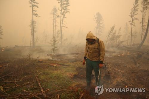 지난 17일 사하공화국의 한 화재 현장에서 당국자가 진화작업을 펼치는 모습. [로이터=연합뉴스]