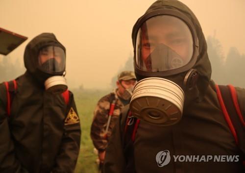 지난 17일 사하공화국의 산불 현장에서 마스크를 쓴 소방당국 관계자들. [AP=연합뉴스]