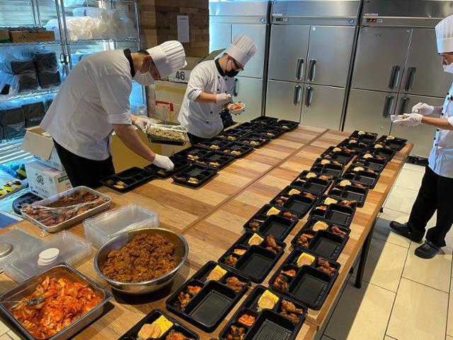 일본 도쿄올림픽에 출전한 한국 선수단을 지원하는 대한체육회의 현지 급식지원센터에서 20일 조리사들이 음식을 도시락 용기에 담고 있다. 우라야스=연합뉴스