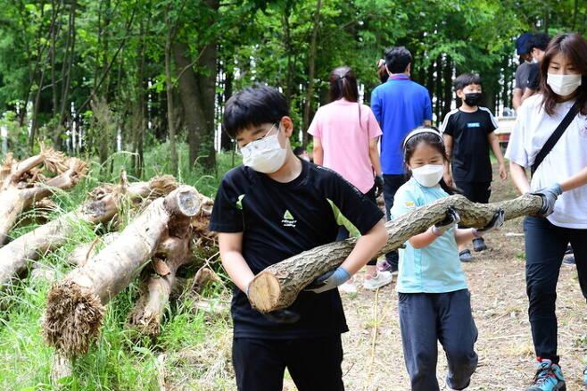 곡성 오산초등학교 곽찬훈군이 지난 6월 섬진강 제월섬에서 진행된 트리하우스 만들기 프로그램에 참여해 통나무를 함께 옮기고 있다. 곡성교육지원청 제공