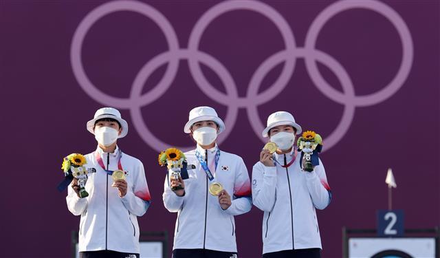 한국 여자 양궁 대표팀 안산(왼쪽부터), 장민희, 강채영 선수가 25일 일본 도쿄 유메노시마 공원 양궁장에서 열린 여자 양궁 단체전에서 금메달을 딴 뒤 시상식에 올라 금메달을 들어보이고 있다.도쿄 올림픽사진공동취재단