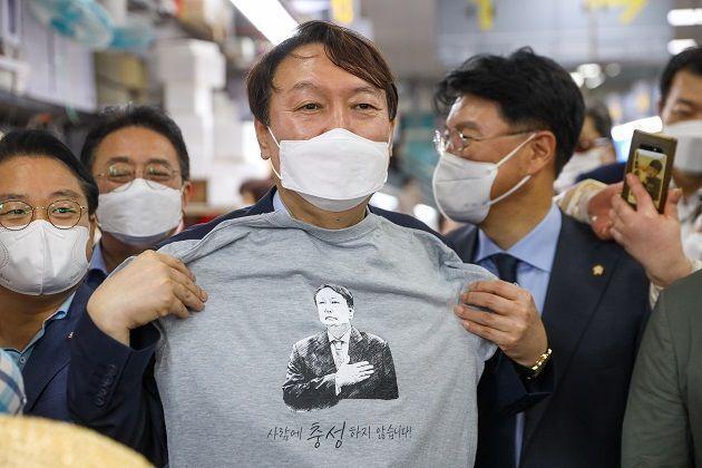 윤석열 전 검찰총장이 27일 부산 자갈치시장에서 '사람에 충성하지 않습니다'란 문구와 자신의 얼굴이 인쇄된 티셔츠를 들어 보이고 있다. ⓒ윤석열 캠프