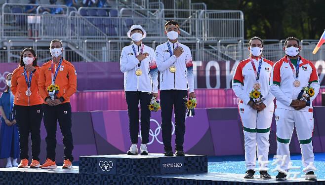 '2020 도쿄올림픽' 양궁 혼성 단체전에서 금메달을 획득한 김제덕, 안산이 24일 오후 일본 도쿄 유메노시마 공원 양궁장에서 애국가를 부르고 있다. 올림픽사진공동취재단