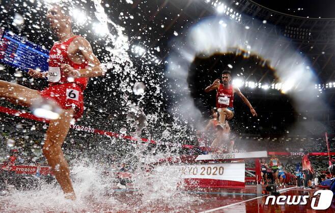 2일 도쿄 올림픽 스타디움에서 장애물 달리기 선수들이 비를 뚫고 금빛 레이스를 펼치고 있다. © 로이터=뉴스1 © News1