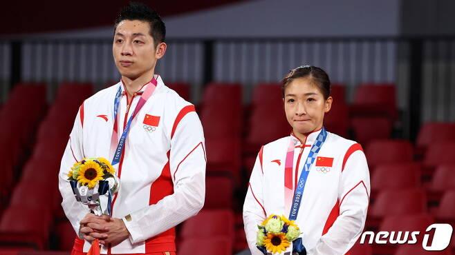 중국 탁구 혼합 복식조가 은메달을 따 시상대에 올랐지만 표정이 어둡다. © 로이터=뉴스1 © News1 박형기 기자