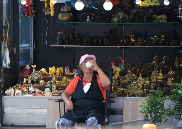 3일 오후 종로구 창신동 동대문역 부근의 '거리 가게' 앞에서 한 상인이 냉수 한 컵으로 더위를 식히고 있다. 왕태석 선임기자
