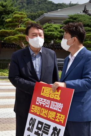 윤석열(왼쪽) 전 검찰총장이 4일 오전 서울 종로구 청와대 분수대 앞에서 '드루킹 여론 조작'에 대한 문재인 대통령 사과를 촉구하는 1인 릴레이 시위를 하는 권성동 국민의힘 의원과 이야기를 나누고 있다. 국회사진기자단