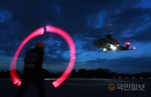 """인천 영종도 해경 항공구조대 활주로에서 지난 19일 헬기가 야간 순찰 비행을 위해 이륙하고 있다. 붉은 원처럼 보이는 것은 신호수가 양손에 지시봉을 들고 머리 위로 올렸다 내리기를 반복하며 이륙신호를 보내는 모습. 3700시간 조종 경력을 가진 항공구조대 이진보 경감은 """"야간의 해상에선 시야가 차단돼 비행착각을 일으키기 쉽다""""며 야간 작전의 위험성을 설명했다."""