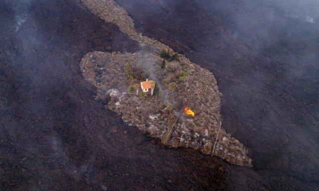 20일 스페인 카나리아스의 라 팔마 섬 라스 만차스 근처에서 화산이 폭발한 후 흘러내린 용암이 가옥들을 삼키고 있다. AP=뉴시스