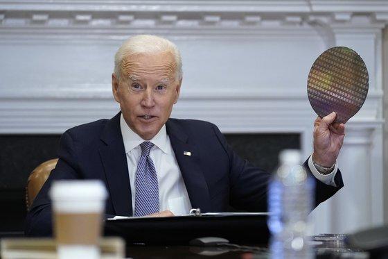 조 바이든 미국 대통령이 지난 4월 백악관에서 열린 반도체 CEO 서밋에서 웨이퍼를 들어 보이고 있다. [AP=연합뉴스]