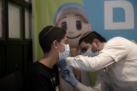 이스라엘 예루살렘의 시네마시티 멀티플렉스 극장에 마련된 코로나19 백신 접종센터에서 22일(현지시간) 14세 소년이 코로나19 백신 부스터샷을 맞고 있다. AP뉴시스