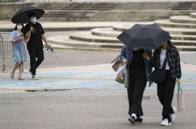 지난 27일 오후 서울 서초구 반포한강시민공원에서 갑자기 내린 비에 시민들이 우산을 쓰고 발걸음을 옮기고 있다. /뉴시스
