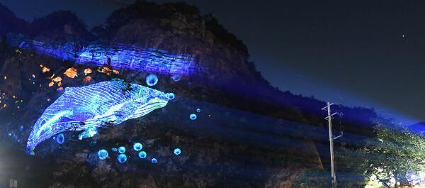 강원도 원주 간현암에 고래가 유영하는 영상이 비춰지고 있다. 형형색색 빛의 향연은 바위와 절벽을 예술의 무대로 탈바꿈시킨다.