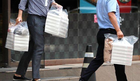 신종 코로나바이러스 감염증(코로나19) 확산으로 서울 등 수도권 지역에 사회적 거리두기 4단계가 시작된 지난 7월 12일 서울 여의도의 한 식당에서 시민들이 음식을 포장한 음식을 들고 음식점을 나서고 있다. 뉴스1