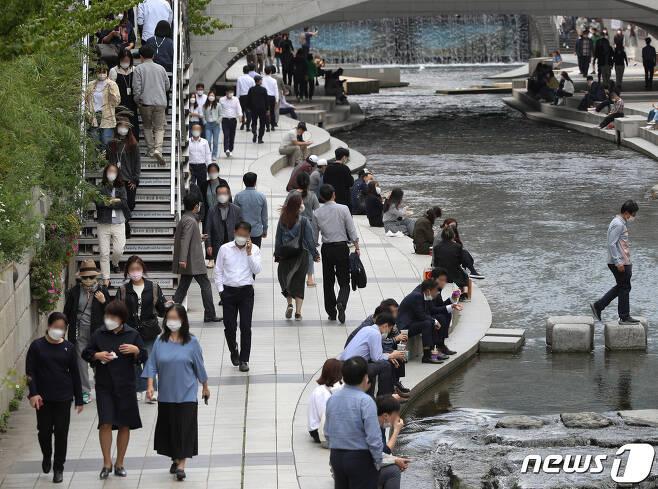 14일 오후 서울 중구 청계천에서 직장인들이 점심시간을 이용해 휴식을 취하고 있다. 신종 코로나바이러스 감염증(코로나19) 확산 방지를 위해 오는 18일부터 적용될 사회적 거리두기 조정안이 15일 발표된다. 2021.10.14/뉴스1 © News1 신웅수 기자