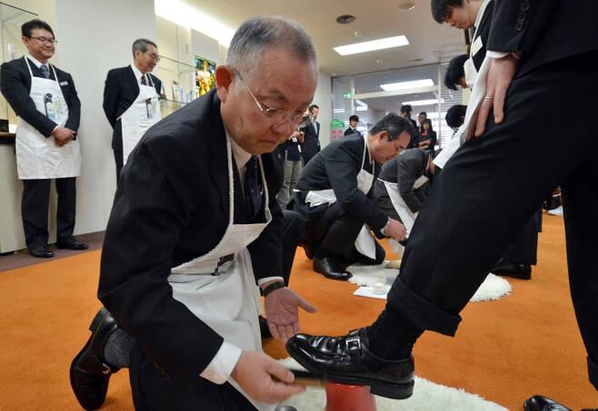 일본의 한 구두약 제조사 시니어 직원이 신입 사원에게 제품 사용법 등을 전수하고 있다. /사진=AFP